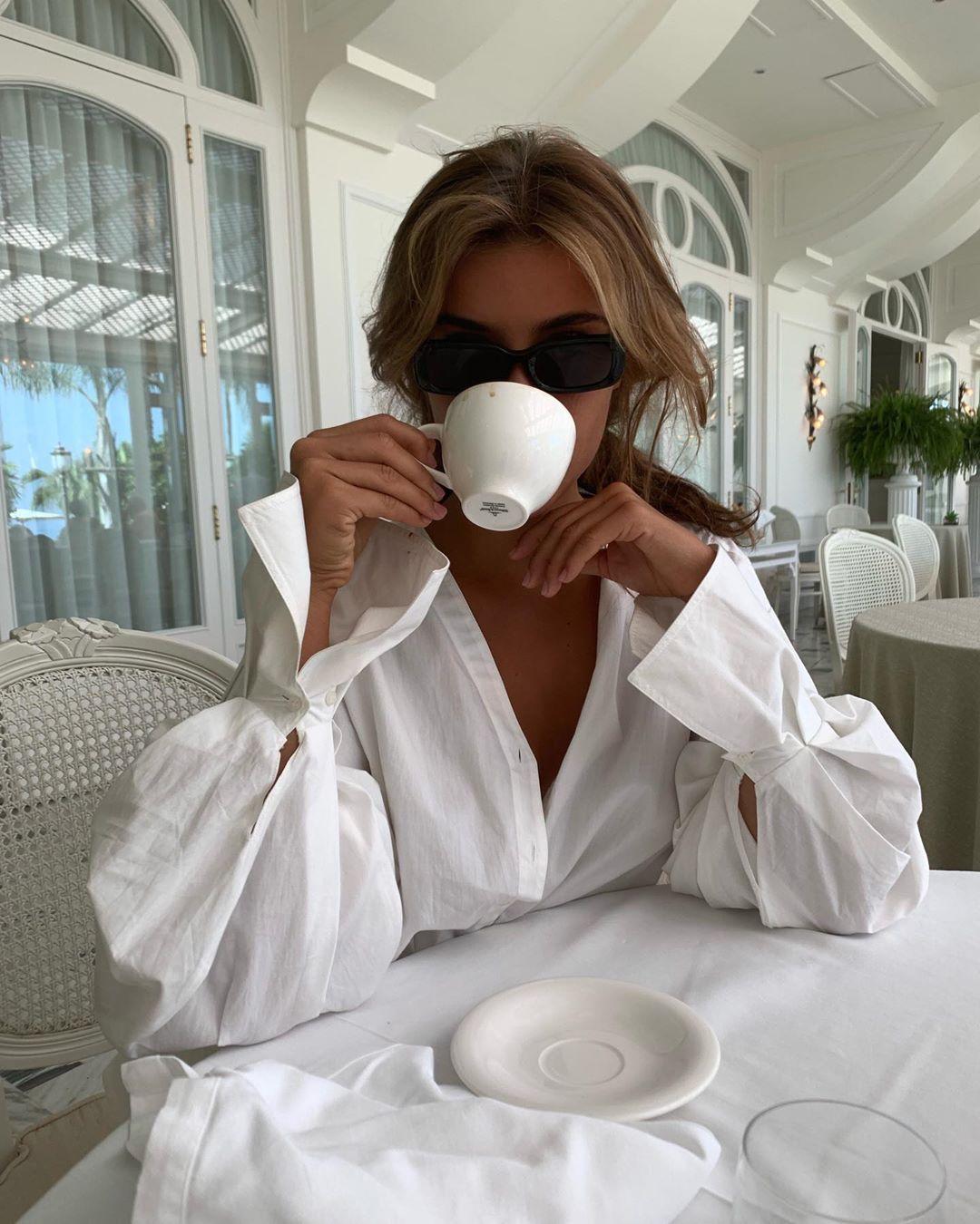 Стильная девушка в темных очках пьет кофе